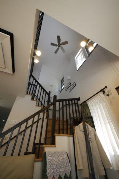 吹抜けリビングに木製欄干手すりのオープン階段がある家